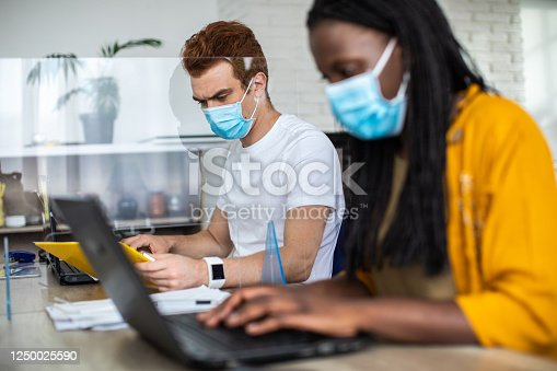 1124783373 istock photo Coworkers with protective face masks using laptops at modern office 1250025590