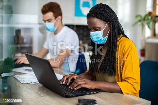 1124783373 istock photo Coworkers with protective face masks using laptops at modern office 1250025658