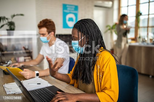 1124783373 istock photo Coworkers with protective face masks using laptops at modern office 1250025693