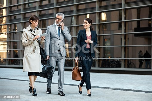 Full length of coworkers with digital tablet and smart phone walking on street. Confident businessman and businesswomen are discussing in city. Entrepreneurs in businesswear are carrying bags.