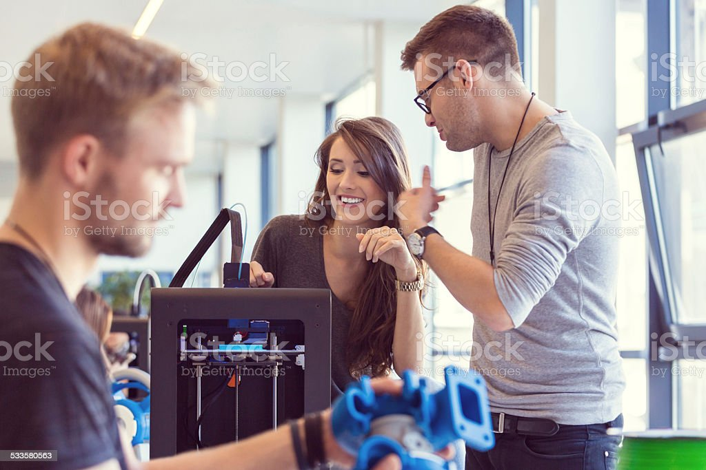 Coworkers working in an 3D printer office Start-up business team working in an office. Focus on two coworkers using a 3D printer, while the man in the foreground watching 3D printout. 2015 Stock Photo