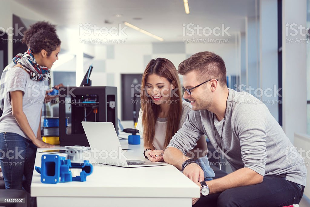 Coworkers working on laptop in 3d printer office Start-up business team working together in 3D printer office. Focus on smiling two young people using a laptop. 2015 Stock Photo
