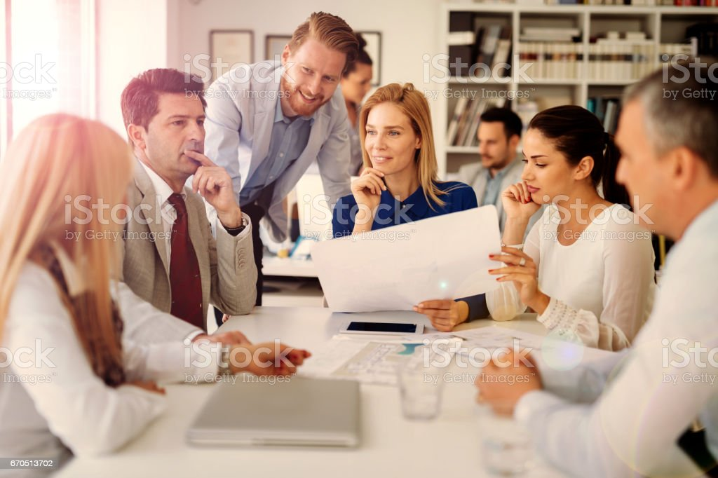 Coworkers working on project together in office Coworkers working on project together in office Accountancy Stock Photo