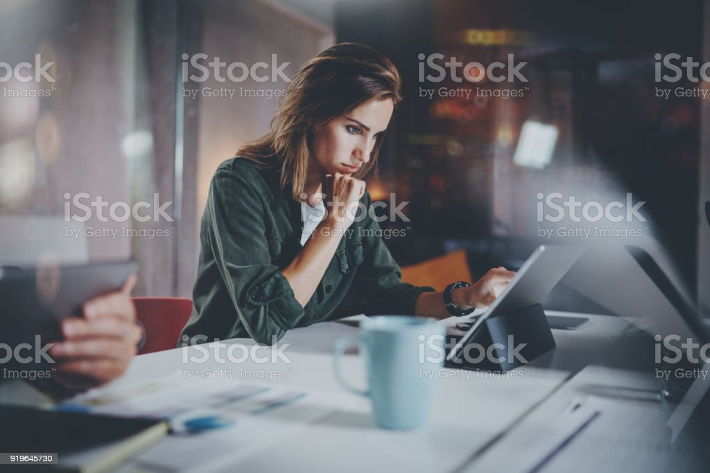 プロセス写真を作業の協力者。同僚と一緒に夜の近代的なオフィスのロフトで働く若い女性。チームワークの概念。背景をぼかし。水平。 ロイヤリティフリーストックフォト