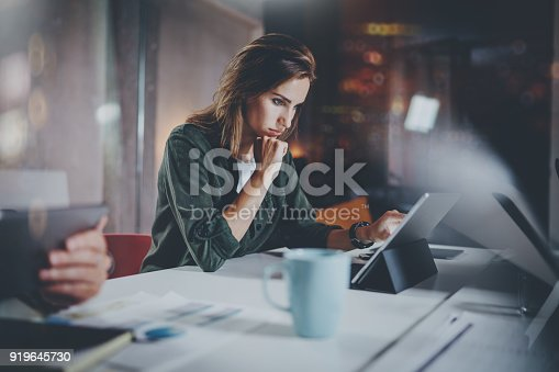 istock Coworkers working process photo.Young woman working together with colleagues at night modern office loft.Teamwork concept.Blurred background.Horizontal. 919645730