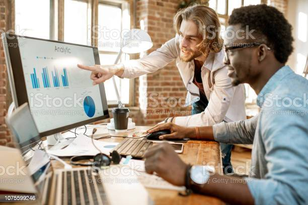 Coworkers Working With Analytics In The Office Stock Photo - Download Image Now
