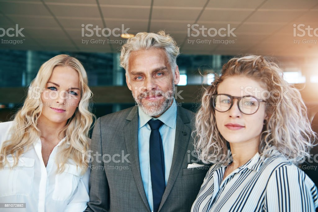 Contemporary business men and women standing together in office and...