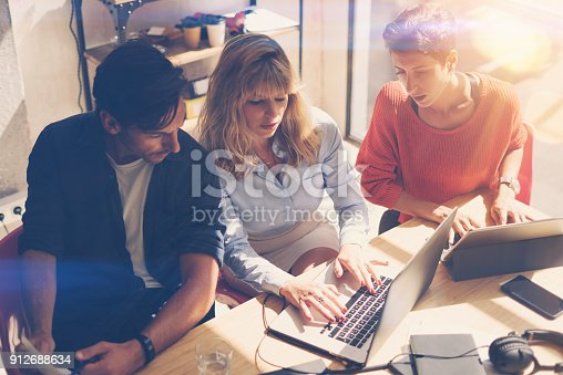 912675036 istock photo Coworking process at sunny office.Business team sitting at meeting room and using mobile devices.Horizontal.Blurred background. 912688634