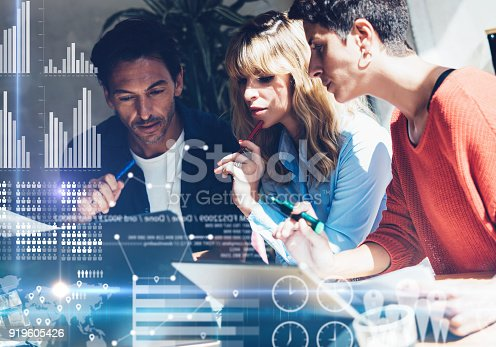 istock Coworking process in a sunny office.Young Business team making discussing at office.Concept of digital diagram,graph interfaces,virtual screen,connections icon.Horizontal,blurred background. 919605426