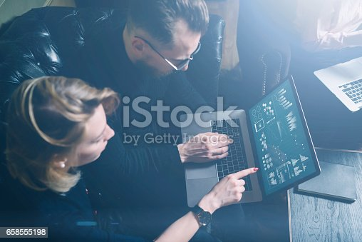 istock Coworking process in office.Two young colleagues using computer.Woman wearing black pullover and sitting on the sofa.Graphs,online interfaces and diagramm on laptop screen.Horizontal, visual effects. 658555198