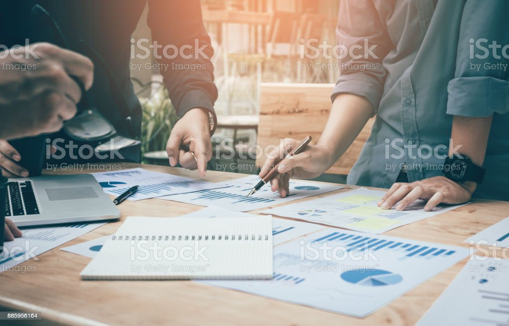 Co-working space office with group start-up analysis to data paper chart on desk. stock photo