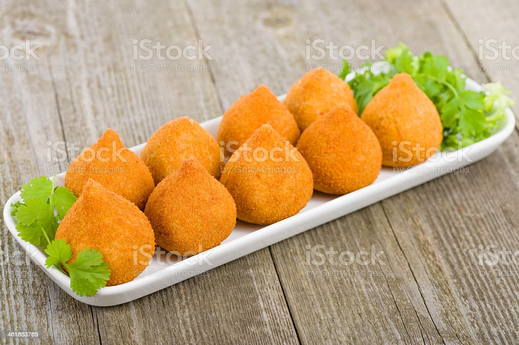 Coxinha de Galinha on a white plate placed on a wooden table stock photo