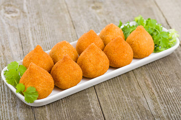 coxinha de galinha on a white plate placed on a wooden table - coxinha stock photos and pictures