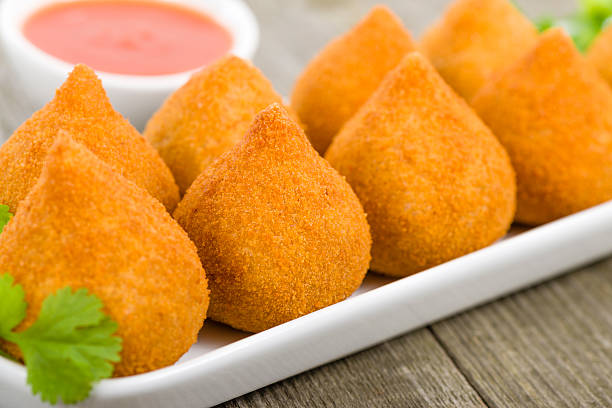 Coxinha de Galinha on a wooden table with sauce Coxinha de Galinha - Brazilian deep fried chicken snack, popular at local parties. Served with chili sauce. coxinha stock pictures, royalty-free photos & images