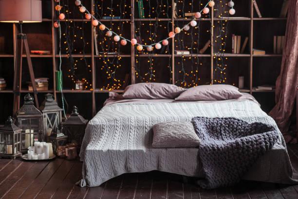 gemütlichkeit, komfort, innenraum und feiertagen konzept - gemütliches schlafzimmer mit bett und garland lichter zu hause. ein rack mit bücher hinter dem bett. kerzen, eine lampe und eine lampe stehen neben dem bett. handgestrickte plaid - schlafzimmer beleuchtung stock-fotos und bilder