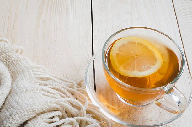 cozy and soft winter background. tea and warm knitted blanket. - heiße zitrone stock-fotos und bilder