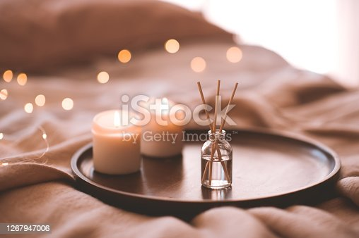 Aroma bamboo sticks in bottle with scented liquid with candles staying on wooden tray in bed closeup.