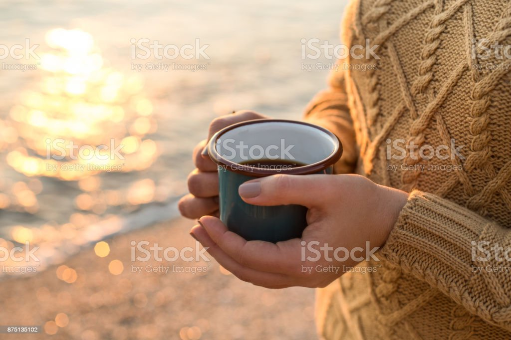 Cozy autumn by the sea. Female hands holding a mug with tea stock photo