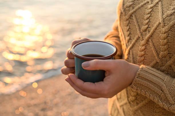 outono aconchegante à beira-mar. femininas mãos segurando uma caneca com chá - chá bebida quente - fotografias e filmes do acervo