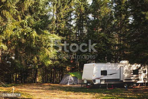 A camper trailer and tent surrounded by tall pine trees parked in a deserted campsite in a autumn daytime landscape