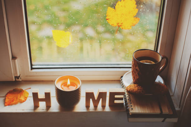 cozy autumn morning at home. Hot tea and candle on window in rainy cold day. Spending holidays at home. stock photo