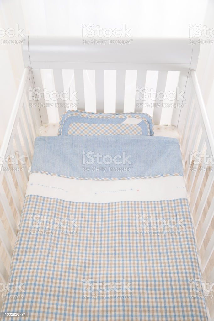 Cozy baby cot with white square pillows and patchwork comforter...