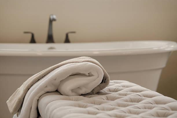 gemütliches badezimmer mit handtüchern auf die gepolsterte sitzbank - gepolsterte bank stock-fotos und bilder