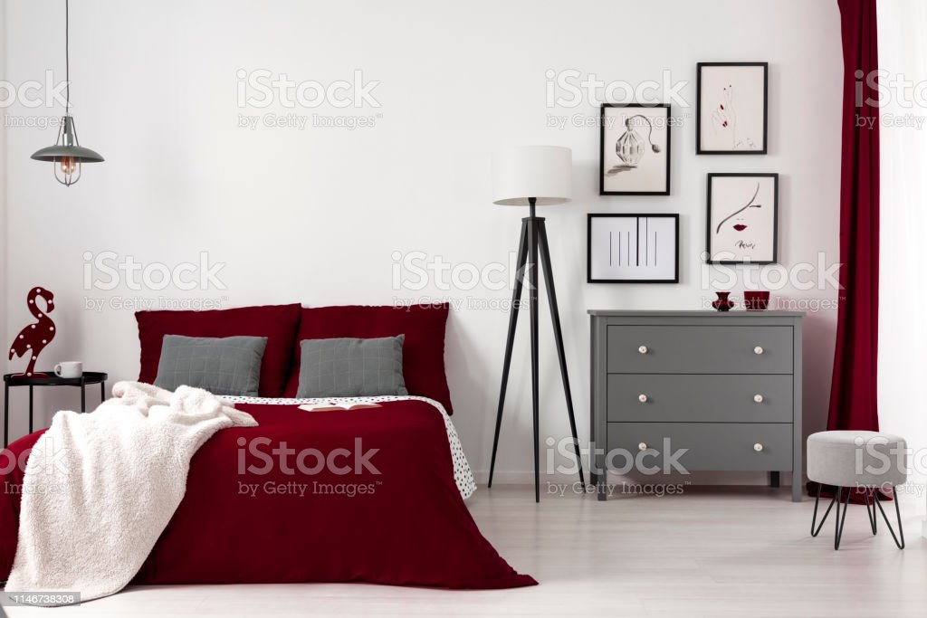 Cozy bed with burgundy bedding, grey pillows and white fury blanket...