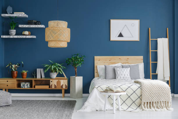 Cozy bedroom interior Cozy bedroom interior with a double bed, wooden cabinet, chandelier and blue wall bedroom stock pictures, royalty-free photos & images