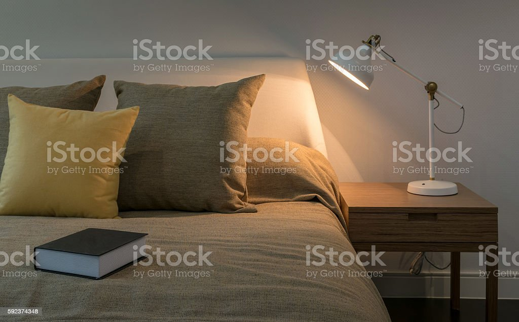Cozy bedroom interior with book and reading lamp on table stock photo
