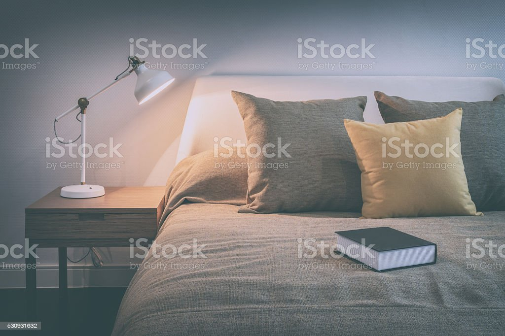 cozy bedroom interior with book and reading lamp