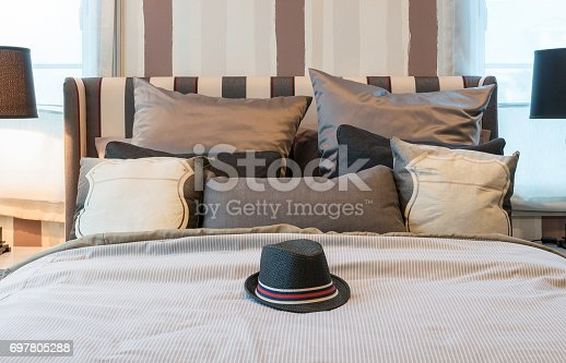 cozy bedroom interior with dark brown pillows and black hat on bed