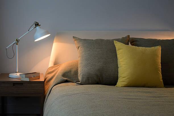 gemütliche schlafzimmer interieur mit kissen und leselampe - nachttischleuchte stock-fotos und bilder