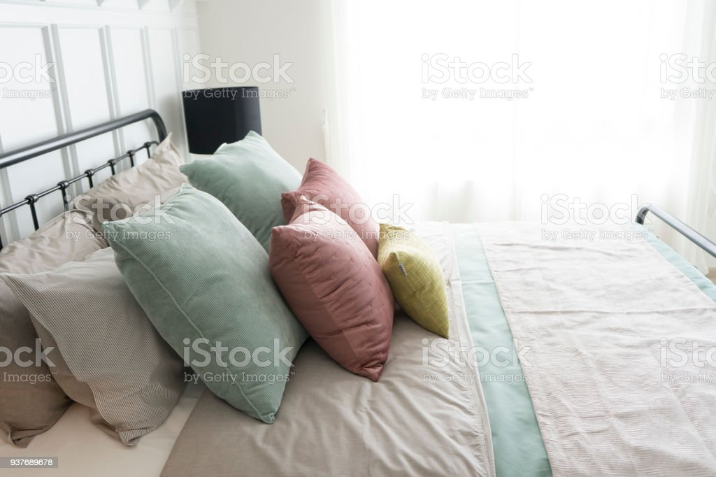 cozy bedroom with pastel pink and green accents pillows. stock photo