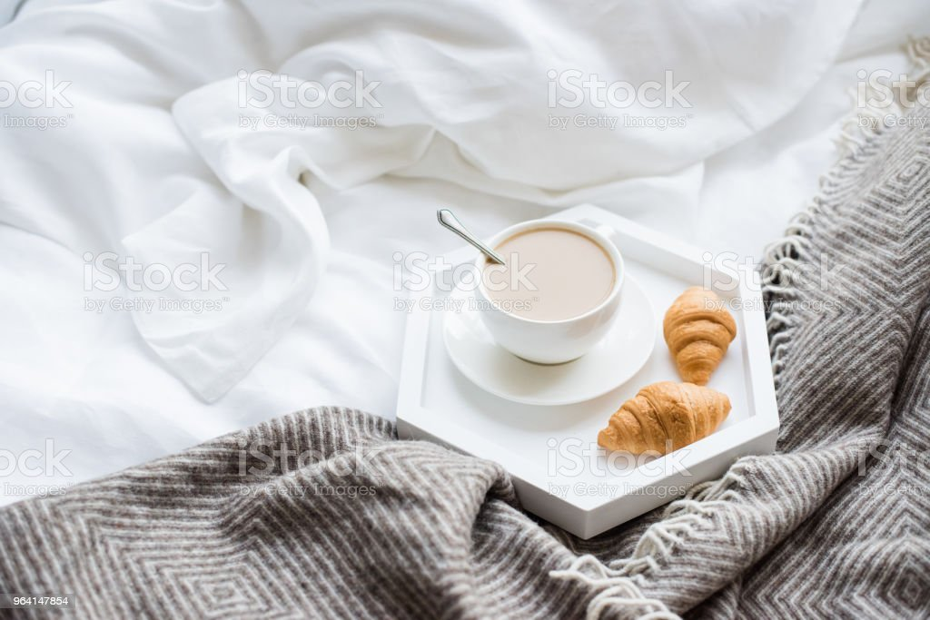 Cozy breakfast in bed, cup of coffee and croissants on white and stock photo