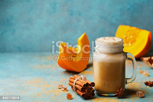 Pumpkin spiced latte or coffee in glass on turquoise vintage table. Autumn, fall or winter hot drink. Cozy breakfast or snack.
