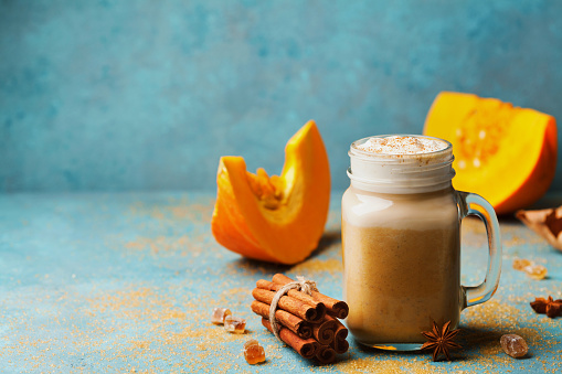 istock Cozy breakfast or snack from pumpkin spiced latte or coffee in glass on turquoise vintage table. Fall or winter hot drink. 840173918