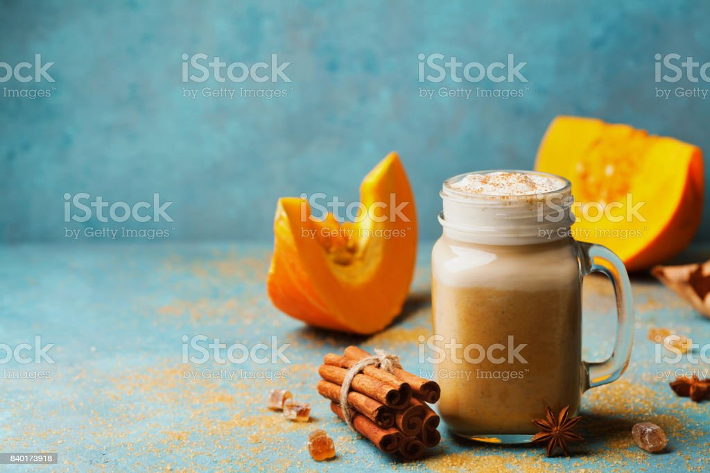 Cozy breakfast or snack from pumpkin spiced latte or coffee in glass on turquoise vintage table. Fall or winter hot drink. stock photo