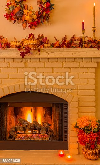 istock Cozy Brick fireplace with fall decorations and candles (P) 834021808