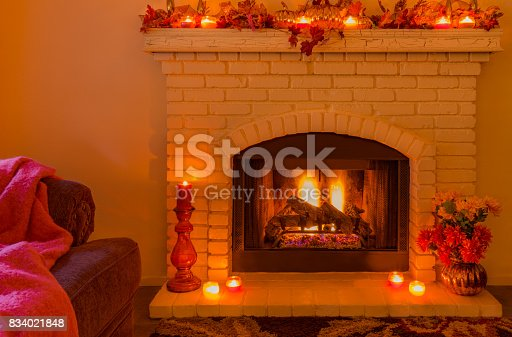 istock Cozy Brick fireplace with fall decorations and candles (P) 834021848