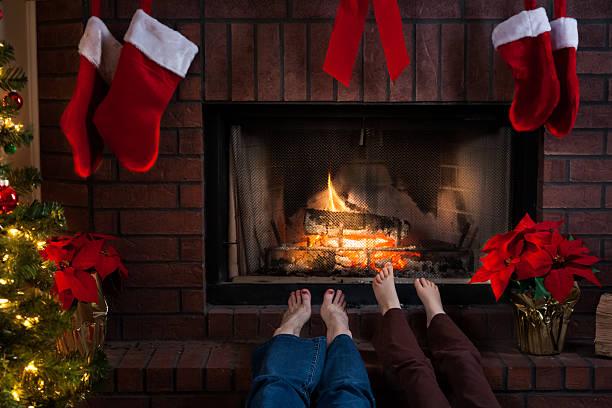 gemütliche weihnachten kamin mit großmutter und enkelin warme füße - granny legs stock-fotos und bilder
