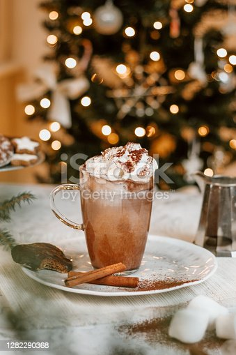 Christmas Hot Chocolate with marshmallows, cookies and Christmas tree in rustic kitchen