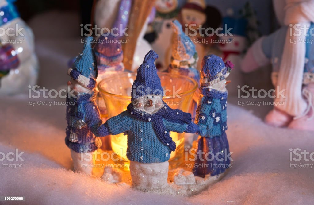 Cozy Christmas Snowmen Five snowman figures dressed in sweater and cap holding hands in a circle.  Each faces away from a central lighted candle in a Christmas tableau. Blue Stock Photo