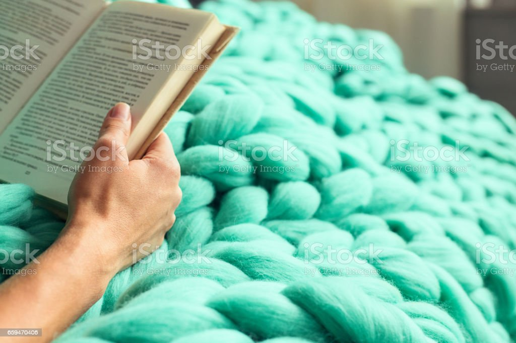Cozy composition, closeup of woman reading book on merino wool plaid having a rest, warm and comfortable atmosphere stock photo