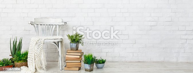 Cozy corner. Chair and plants on books over white brick wall, blank space