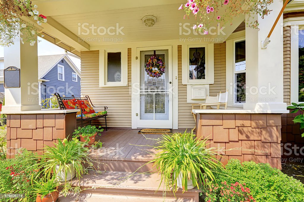 Cozy covered porch with white columns in American craftsman house American craftsman house exterior. Cozy covered porch with white columns and lots of flowers in the front. Architectural Column Stock Photo