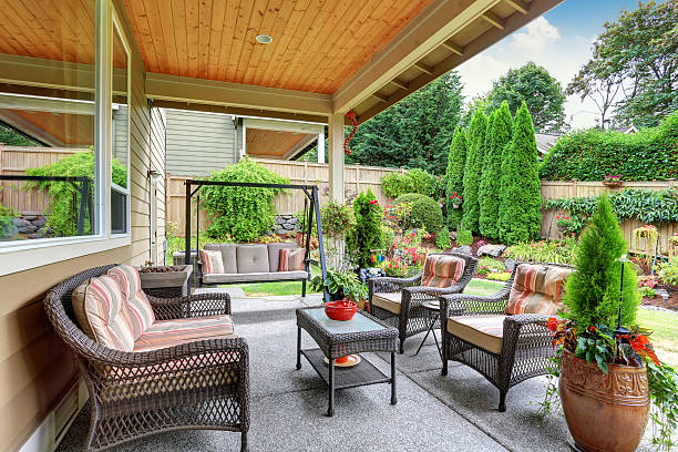 cozy covered sitting area with wicker chairs and swing - patio stock photos and pictures