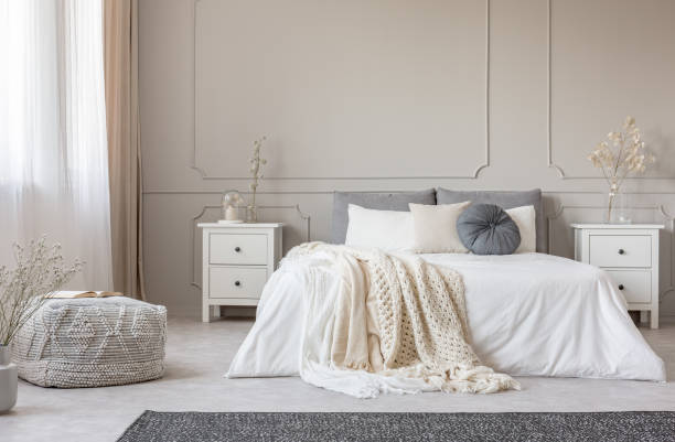 Cozy cream colored woolen blanket on king size bed in bright bedroom – zdjęcie