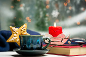 Cozy cup of coffee with Christmas decorated cookie and festive background