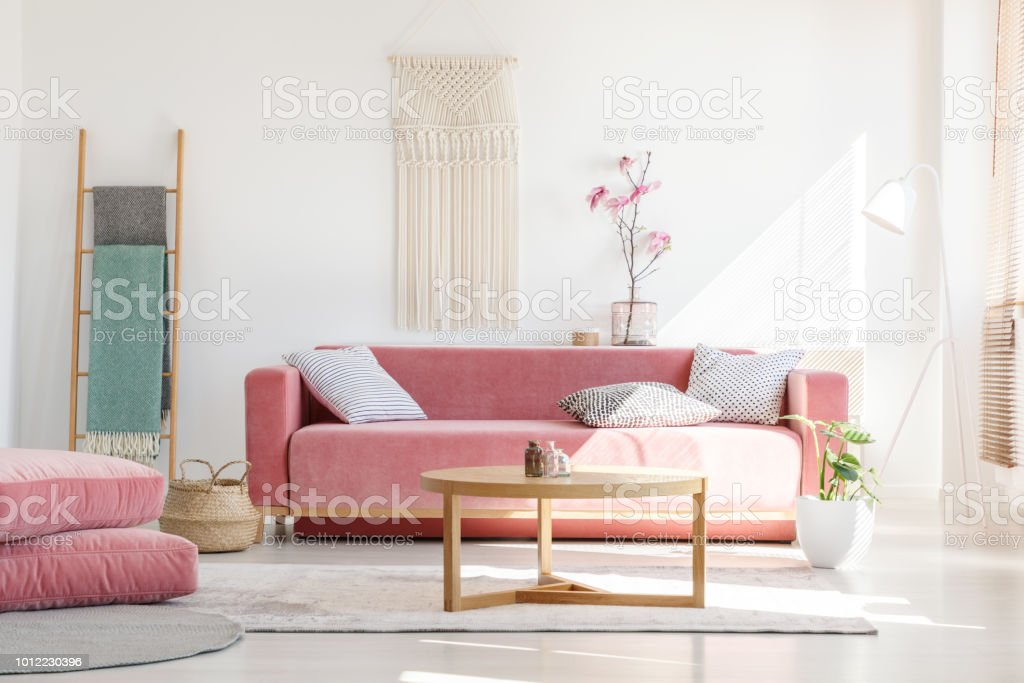 Cozy cushions and stylish textiles in a sunny, feminine living room interior with a pink, velvet sofa and a macrame on a white wall stock photo